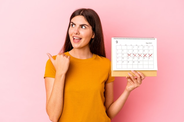 Young caucasian woman holding calendar isolated on pink background points with thumb finger away, laughing and carefree.