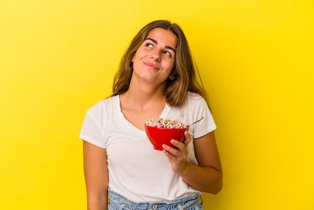 目標と目的を達成することを夢見て黄色の背景に分離された穀物を保持している若い白人女性