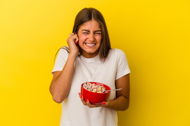 Young caucasian woman holding cereals isolated on yellow background covering ears with hands.