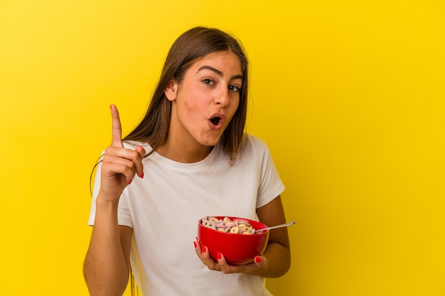 Young caucasian woman holding cereals isolated on yellow background having an idea, inspiration concept.