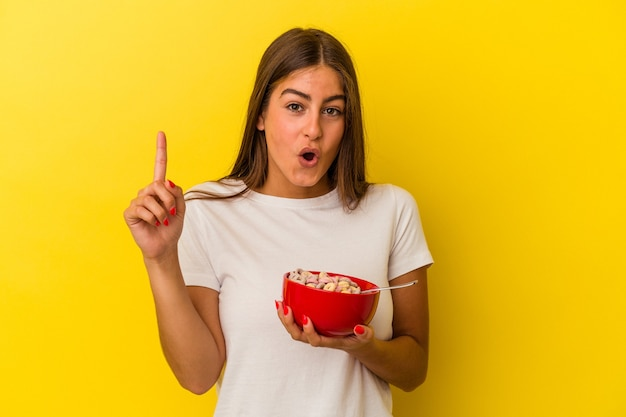 Young caucasian woman holding cereals isolated on yellow background having some great idea, concept of creativity.