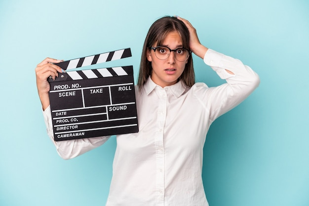 Young caucasian woman holding clapperboard isolated on blue background being shocked, she has remembered important meeting.