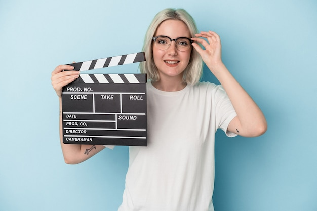Young caucasian woman holding a clapperboard isolated on blue background excited keeping ok gesture on eye.