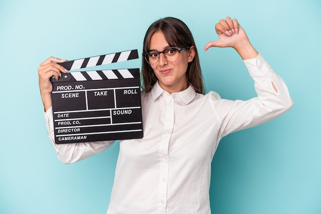 Young caucasian woman holding clapperboard isolated on blue background feels proud and self confident, example to follow.