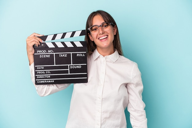Young caucasian woman holding clapperboard isolated on blue background happy, smiling and cheerful.