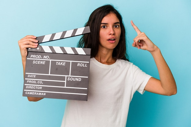 Young caucasian woman holding a clapperboard isolated on blue background having an idea, inspiration concept.