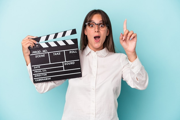 Young caucasian woman holding clapperboard isolated on blue background having an idea, inspiration concept.