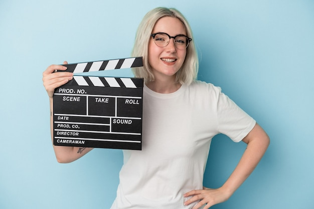Young caucasian woman holding a clapperboard isolated on blue background laughing and having fun.