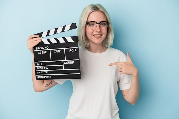 Young caucasian woman holding a clapperboard isolated on blue background person pointing by hand to a shirt copy space, proud and confident