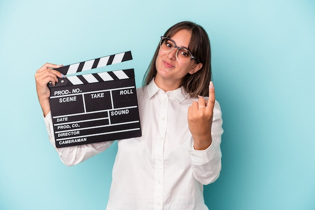Young caucasian woman holding clapperboard isolated on blue background pointing with finger at you as if inviting come closer.