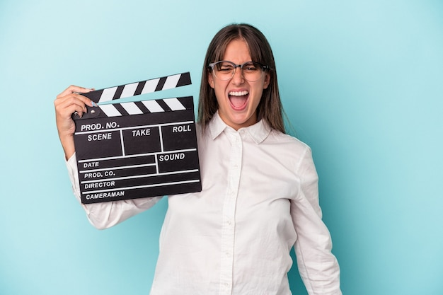 Young caucasian woman holding clapperboard isolated on blue background screaming very angry and aggressive.