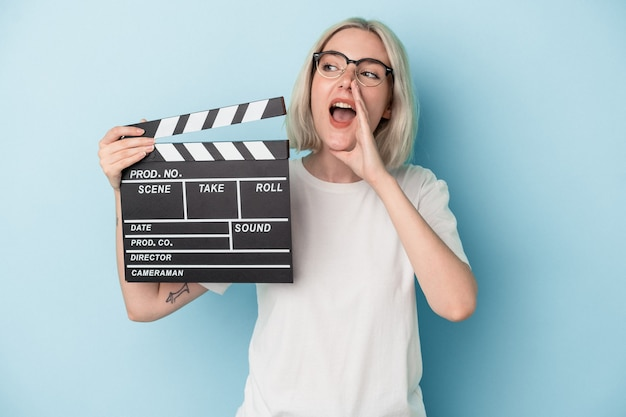 Young caucasian woman holding a clapperboard isolated on blue background shouting and holding palm near opened mouth.