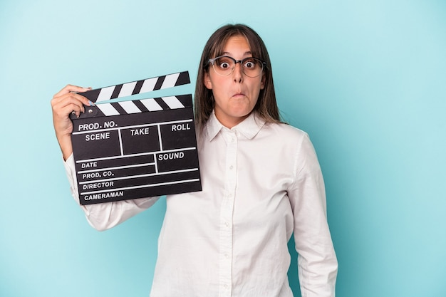 Young caucasian woman holding clapperboard isolated on blue background shrugs shoulders and open eyes confused.