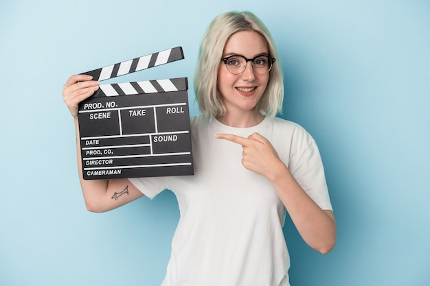 Young caucasian woman holding a clapperboard isolated on blue background smiling and pointing aside, showing something at blank space.