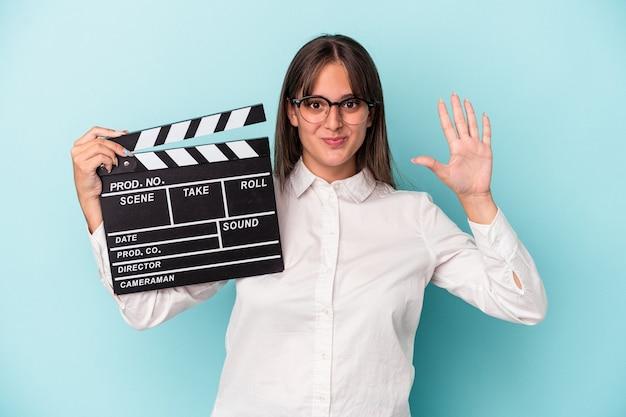 青い背景に分離されたカチンコを持っている若い白人女性は、指で5番を示して陽気に笑っています。