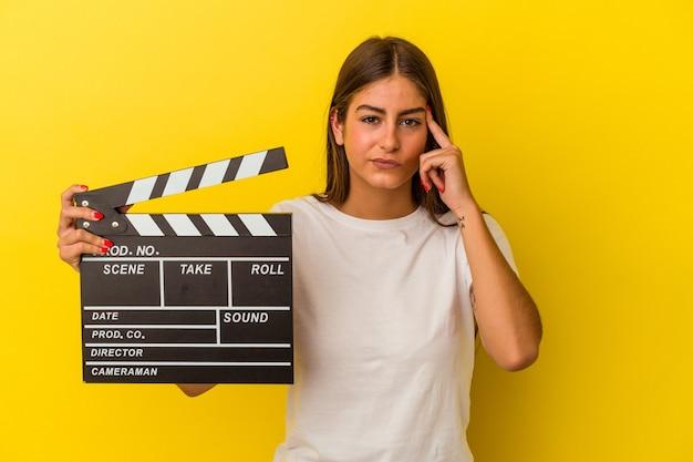 Молодая кавказская женщина, держащая с 'хлопушкой', изолированная на белом фоне, указывая висок пальцем, думая, сосредоточилась на задаче.