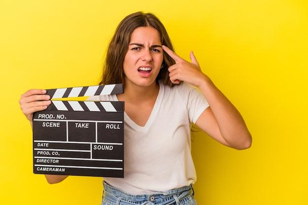 人差し指で失望のジェスチャーを示す黄色の背景に分離されたカチンコを保持している若い白人女性。