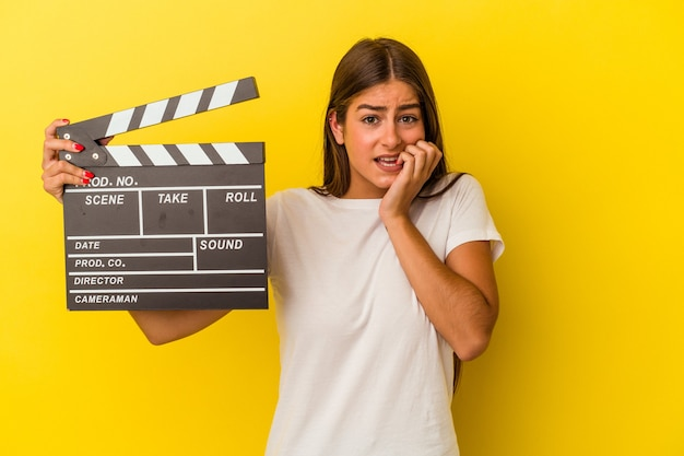 Young caucasian woman holding clapperboard isolated on white background biting fingernails, nervous and very anxious.