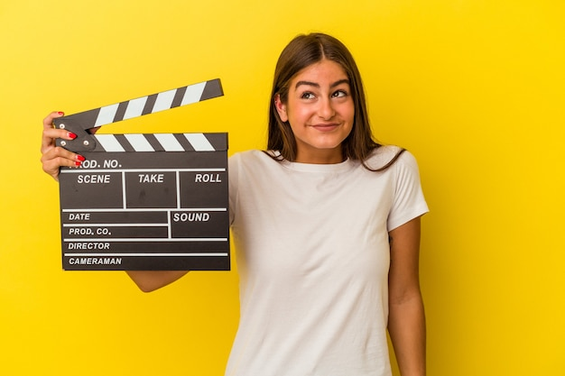Young caucasian woman holding clapperboard isolated on white background dreaming of achieving goals and purposes