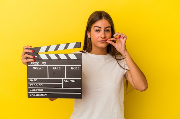 Young caucasian woman holding clapperboard isolated on white background with fingers on lips keeping a secret.
