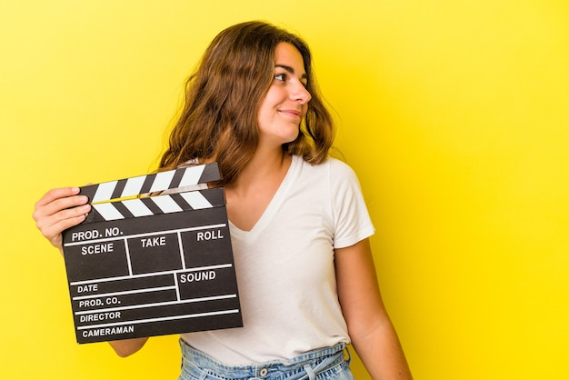 Young caucasian woman holding clapperboard isolated on yellow background  looks aside smiling, cheerful and pleasant.