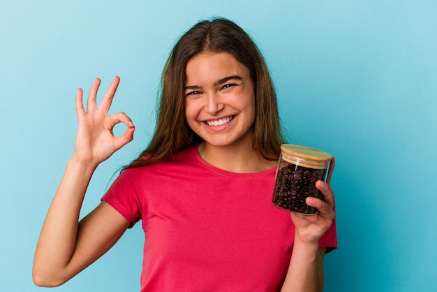 Young caucasian woman holding a coffee jar isolated on blue background cheerful and confident showing ok gesture.