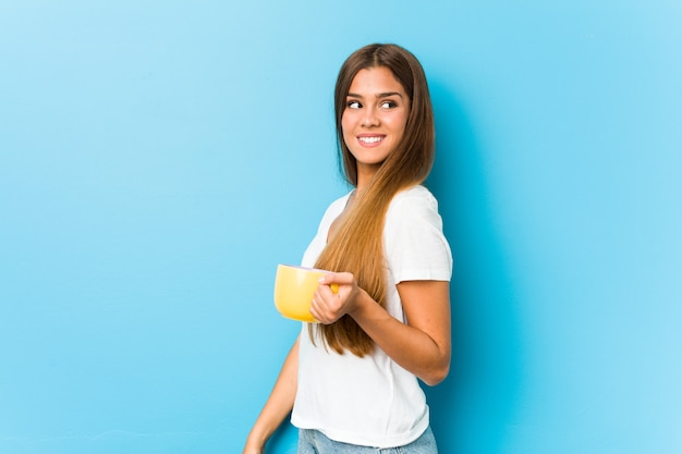 Young caucasian woman holding a coffee mug looks aside smiling, cheerful and pleasant.