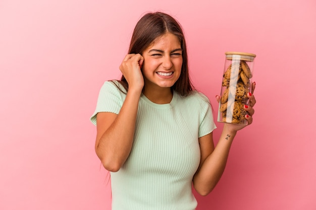 Young caucasian woman holding a cookies jar isolated on pink background covering ears with hands.