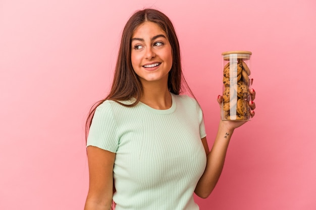 Young caucasian woman holding a cookies jar isolated on pink background looks aside smiling, cheerful and pleasant.