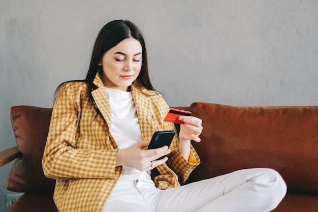 Молодая кавказская женщина, держащая кредитную карту, используя смартфон и делая покупки в интернете.