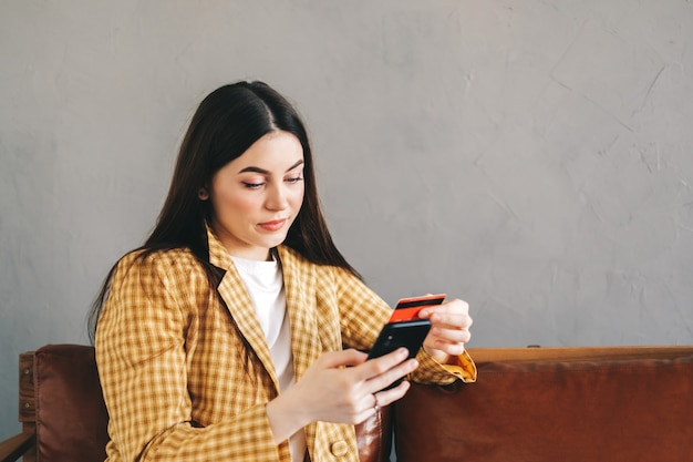 クレジットカードを持って、スマートフォンを使用してオンラインショッピングをしている若い白人女性。