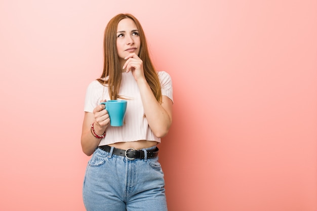 Young caucasian woman holding a cup looking sideways with doubtful and skeptical expression.