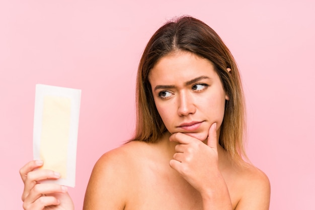 Young caucasian woman holding a depilatory band isolated looking sideways with doubtful and skeptical expression.
