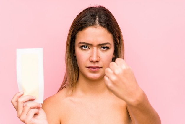 Young caucasian woman holding a depilatory band isolated showing fist with aggressive facial expression.