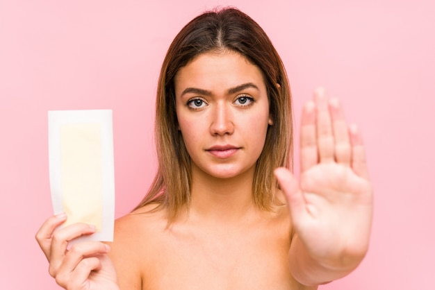 Young caucasian woman holding a depilatory band isolated standing with outstretched hand showing stop sign, preventing you.