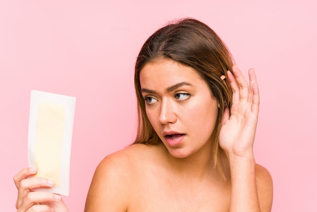 Young caucasian woman holding a depilatory band isolated trying to listening a gossip.