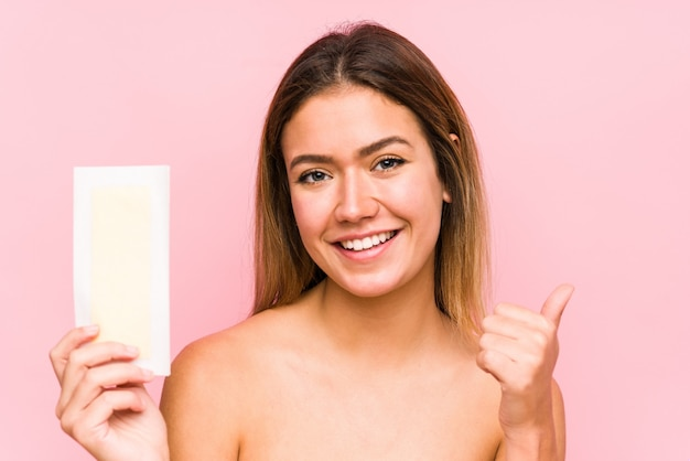 Young caucasian woman holding a depilatory band smiling and raising thumb up