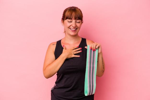 ピンクの背景に分離されたゴムバンドを保持している若い白人女性は、胸に手を置いて大声で笑います。