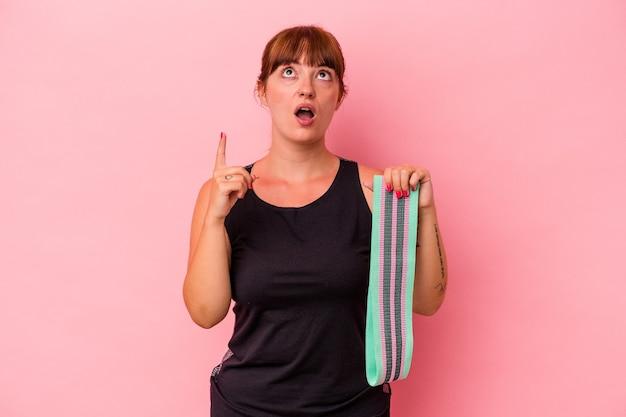 ピンクの背景に分離された弾性バンドを保持している若い白人女性は、口を開けて逆さまを指しています。