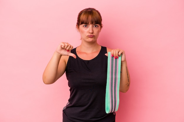ピンクの背景に分離されたゴムバンドを持っている若い白人女性は、嫌いなジェスチャーを示し、親指を下に向けます。不一致の概念。