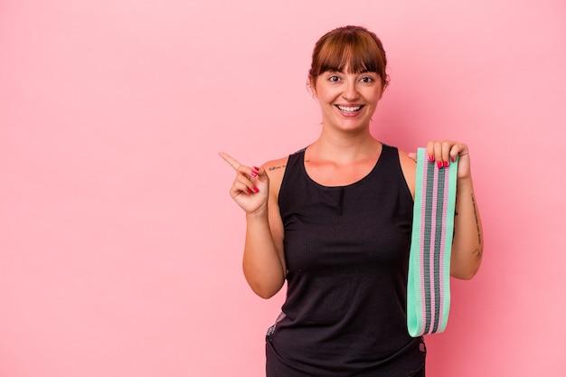 ピンクの背景に分離されたゴムバンドを持って笑顔で脇を向いて、空白のスペースで何かを示している若い白人女性。
