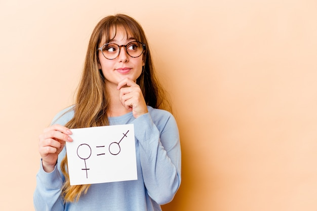 Young caucasian woman holding a equality gender placard isolated looking sideways with doubtful and skeptical expression.