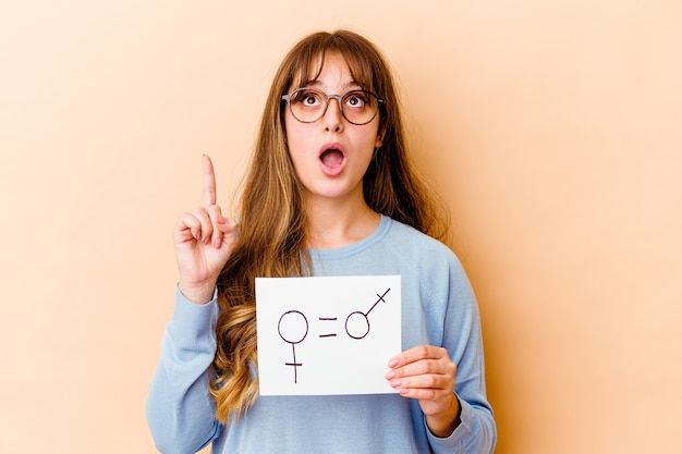Young caucasian woman holding a equality gender placard isolated pointing upside with opened mouth.