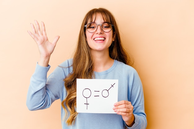 Young caucasian woman holding a equality gender placard isolated receiving a pleasant surprise, excited and raising hands.