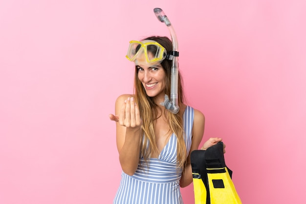 Young caucasian woman holding fins and diving goggles isolated on pink background inviting to come with hand. happy that you came