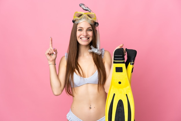 Young caucasian woman holding fins and diving goggles isolated on pink background pointing up a great idea