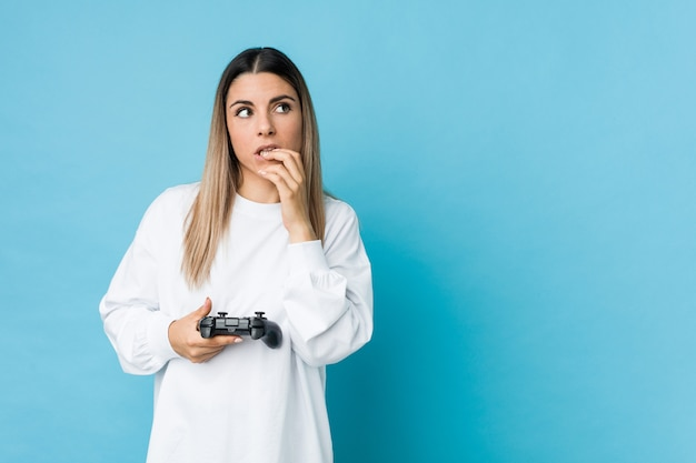 Young caucasian woman holding a game controller relaxed thinking about something looking at a copy space.