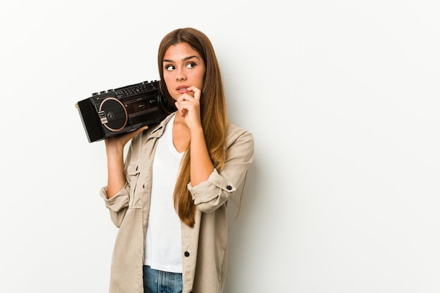 Young caucasian woman holding a ghetto blaster relaxed thinking about something looking at a copy space.