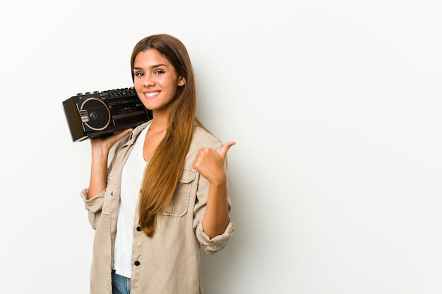 Young caucasian woman holding a ghetto blaster smiling and raising thumb up