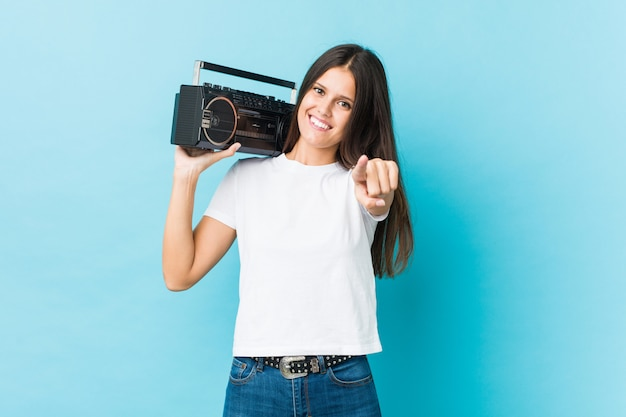 Young caucasian woman holding a guetto blaster cheerful smiles pointing to front.